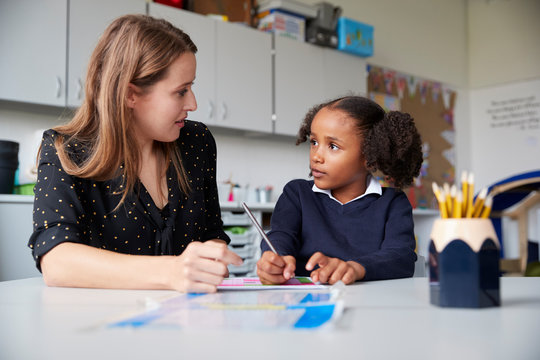 Young female primary school teacher working one on one with a schoolgirl at a table in a classroom, looking at each other, close up