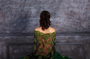 Beautiful girl with curls with a naked back. Back view
