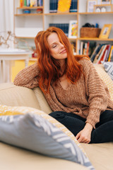 Smiling young woman relaxing on a sofa daydreaming