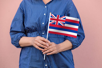 Hawaii state flag. Close up of woman's hands holding Hawaii flag.