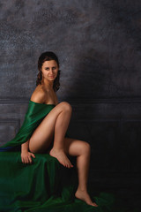 Nude beautiful brunette with green cloth in the studio