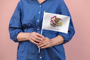Illinois state flag. Close up of woman's hands holding Illinois flag.