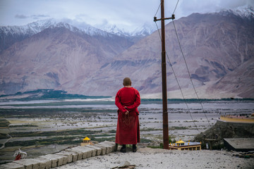 A Buddhist monk overlooked the view of Himalayas and Karakoram ranges in a distance at Diskit Monastery.
