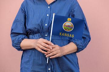 Kansas state flag. Close up of woman's hands holding Kansas flag.