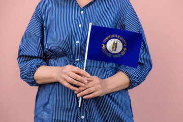 Kentucky state flag. Close up of woman's hands holding Kentucky flag.