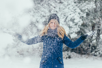 Young attractive beautiful pretty winter woman playing with snow in forest - mademoiselle in fun