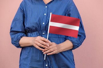 Latvia flag. Close up of woman's hands holding Latvian flag.