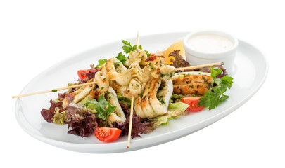 Squid grilled on skewers, with salad and sauce. On white background