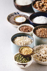 Variety of raw uncooked grains superfood cereal chia seeds, linen, sesame, mung bean, walnuts, tapioca, wheat, buckwheat, oatmeal, coconut, rice in ceramic bowls over grey spotted background.