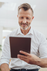 Middle-aged man reading on a tablet computer