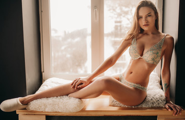 Young sexy woman is sitting on the windowsill in white lingerie.