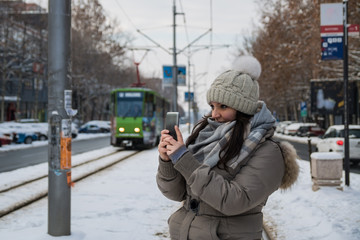 Beautiful women holding mobile phone and waiting for a bus on snow winter day