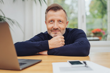 Middle-aged man with dreamy face at computer