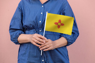 New Mexico state flag. Close up of woman's hands holding New Mexico flag.