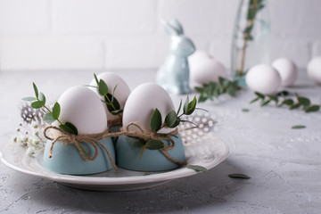 Easter  festive table setting with white chicken  eggs in eggs cups, leaf sprigs of eucalyptus. On a gray concrete background.