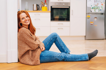 Young woman in sweater sitting on the floor