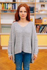 Woman standing and looking at camera emotionlessly