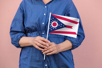 Ohio state flag. Close up of woman's hands holding Ohio flag.