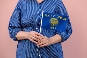 Oregon state flag. Close up of woman's hands holding Oregon flag.