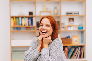 Laughing young redhead woman in her apartment