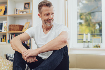 Relaxed mature man sitting on couch at home