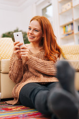 Woman on floor at home looking at her phone