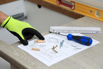 Fototapeta Pracownik pokazuje palcem na rysunku technicznym do montarzu mebli. obraz