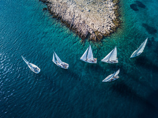 Amazing view of racing sailing boats with small island and crystal clear water