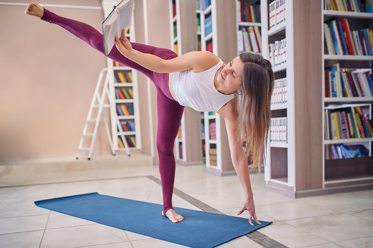 Beautiful young woman reading book and practices yoga asana Ardha Chandrasana - Half Moon pose in the library
