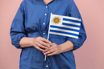 Uruguay flag. Close up of a woman's hands holding Uruguay flag.