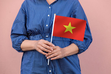 Vietnamese flag. Close up of a woman's hands holding Vietnam flag.