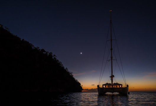 Dark night view on sailing boat anchored on open sea with black silhouette of island