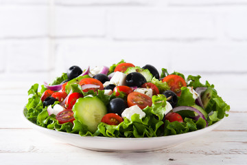 Fresh Greek salad in Plate with black olive,tomato,feta cheese, cucumber and onion on gray background. Top view. Copyspace
