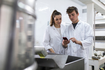 Young woman and young man using mobile in a factory