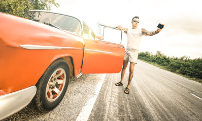 Young hipster fashion man with tattoo taking selfie with vintage car during road trip in Cuba - Travel wanderlust concept always connected on social media influencer lifestyle - Bright retro filter