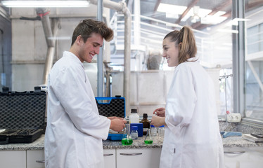 Young man and woman working on a laboratory of factory