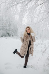 Image of happy blonde woman on walk in winter forest