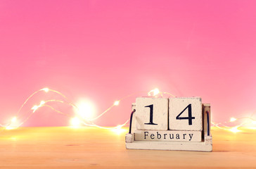 Valentine's day background. Vintage wooden calendar with 14th february date over table and pink bakground.