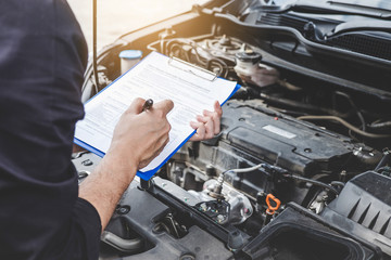 Services car engine machine concept, Automobile mechanic repairman checking a car engine with inspecting writing to the clipboard the checklist for repair machine, car service and maintenance