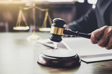 Judge gavel with Justice lawyers, Gavel on wooden table and Counselor or Male lawyer working on a documents. Legal law, advice and justice concept