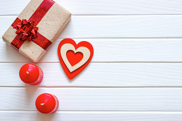 Wooden white background with red hearts, gifts and candles. The concept of Valentine Day. Top view.