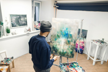 Back of a young artist who works on the picture in his own studio. Talented artist paints an oil painting, a look from the back. Work and hobbies.