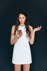 Shocked beautiful woman looking at smartphone