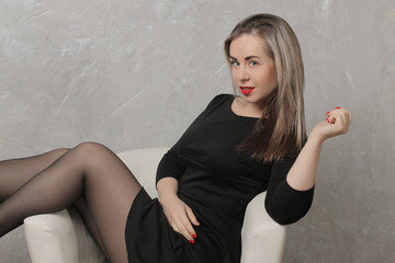 Beautiful girl with red lips and in a black dress sitting in a chair against the background of a gray concrete wall. emotion. different poses