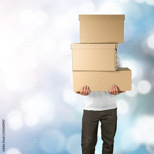 delivery man carrying stacked boxes in front of face against stock
