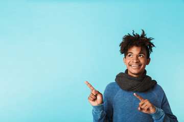 Excited young african man wearing winter scarf Wall mural