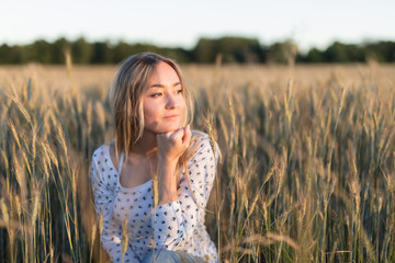 Pretty laty is dreaming in the meadow. Sunset time.