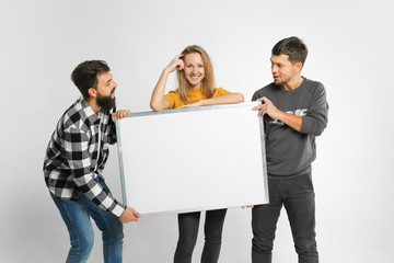 three funny laughing young people wearing casual fashionable clothes, holding mockup big white board isolated in studio, white background. Advertisement concept. Mockup for design