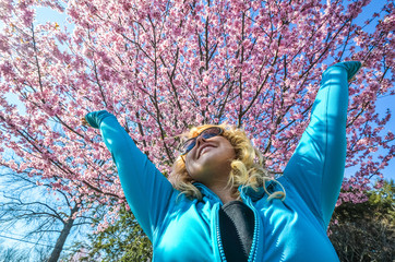 Blonde woman raises her arms up next to a beautiful pink cherry blossom tree and smiles