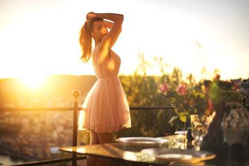 Beautiful girl enjoying the sunset from her terrace